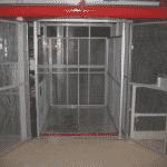Magazijnlift uitgevoerd met blokkeringsklep voor veilig vervoer goederenkarren in een distributiecentrum - De Jong's Liften